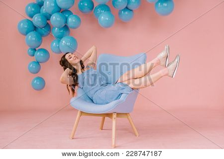 Girl In A Blue Dress In A Pink Room With A Blue Chair And Blue Balls