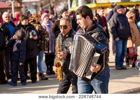 Pernik, Bulgaria - January 26, 2018: Old Street Musician With White Hair And Sunglasses Plays Saxoph