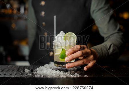 Bartender Hand Holding A Glass Of Splashing Caipirinha Cocktail On The Bar Counter Against Dark Back