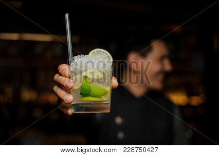 Bartender Hand Holding A Glass Of Caipirinha Cocktail On The Bar Counter Against Dark Background