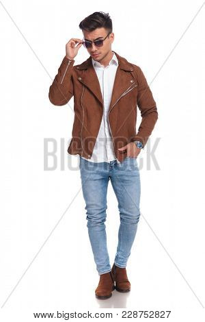 cool young man fixing his sunglasses while standing on white background