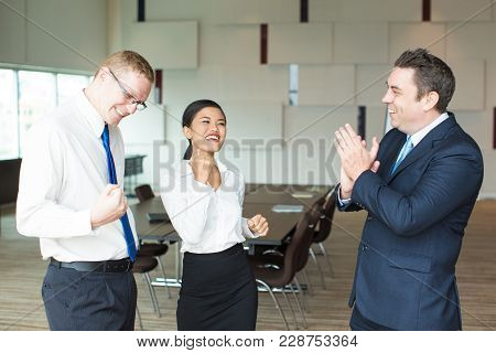 Happy Mid Adult Caucasian Leader Congratulating His Team, Man And Asian Woman, With Success And Appl
