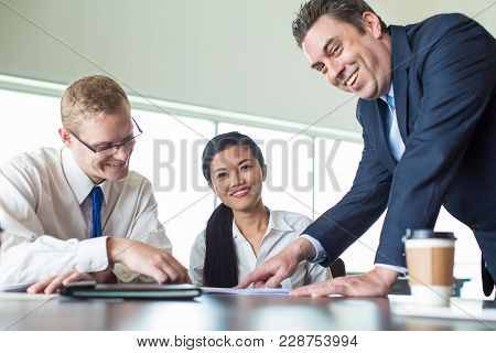 Portrait Of Business Team, Caucasian Mid Adult Executive, Young Man And Asian Woman, Sitting At Meet