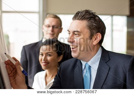 Closeup Of Smiling Businessman Drawing On Flipchart At Business Meeting. Positive Coach Explaining S