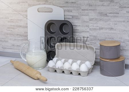 Light Big Kitchen. Tableware For Cooking, Cake Mold And Tray With Eggs On The Table. Jar With Milk.