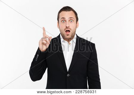 Portrait of adult entrepreneur wearing black suit have spontaneous idea pointing index finger upward isolated over white background