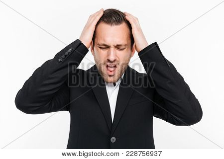Horizontal portrait of tense man in suit grabbing his head being stressed and thinking about solution of problem isolated over white background