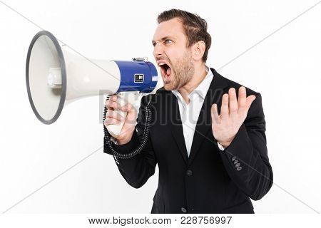 Horizontal image of angry man in business suit screaming in megaphone being stressed isolated over white background