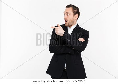 Portrait of surprised man with stubble wearing black suit and pointing index finger aside isolated over white background copy space