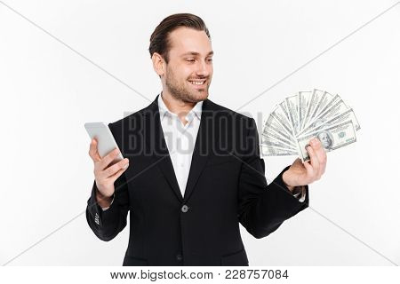 Portrait of rich and fancy man in suit smiling while holding fan of money dollar currency and smartphone in hands isolated over white background