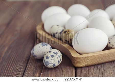 White Eggs And Quail Eggs In Wooden Heart Shaped Plate On Wooden Brown Background, Easter Concept