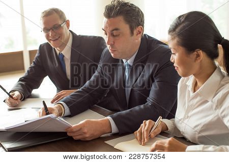 Content Business Man And Woman Looking At Serious Partner Signing Document. Three Business People Cl