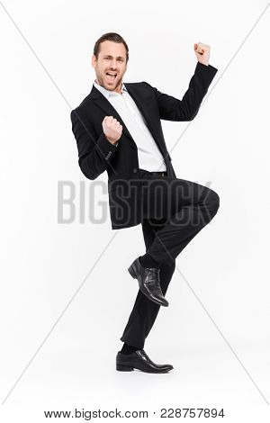 Full-length portrait of ecstatic businessman clenching fists like winner or successful person being happy to reach his goals isolated over white wall