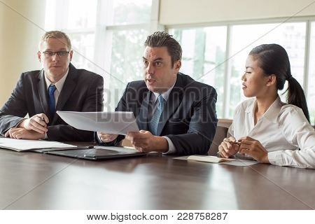 Group Of Three Serious Business People Sitting At Conference Table With Documents. Company Leader Ho