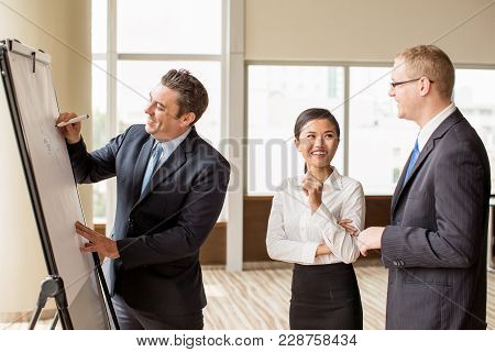 Positive Business Leader Drawing On Flipchart And Explaining Tasks To Employees. Boss Holding Briefi