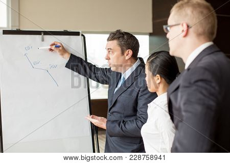 Two Business People Looking At Their Partner Drawing Growth Diagram On Flipchart. Business Team Maki