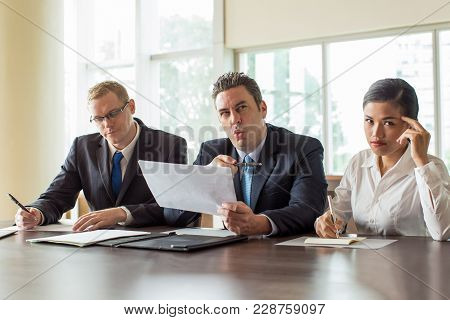 Excited Caucasian Businessman In Suit Speaking And Gesturing While Man In Tie And Young Asian Busine