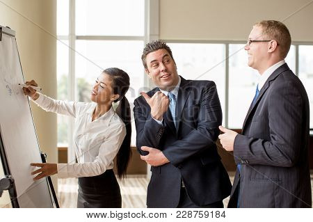 Young Smiling Asian Business Lady Drawing On Flipchart While Two Colleagues Discussing Her Presentat