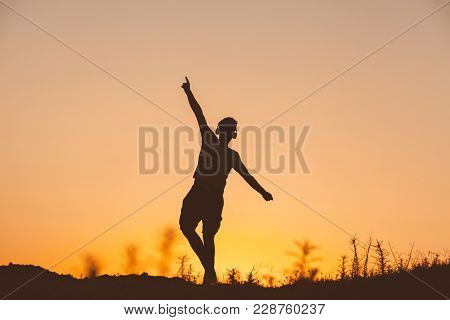 Silhouette Of Man Listening The Music On Sunset Fiery Sky