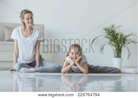 Mother Sitting On Floor With Daughter While She Doing Twine