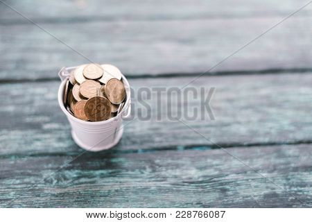 Pennies In An Iron Bucket On A Wooden Old Background