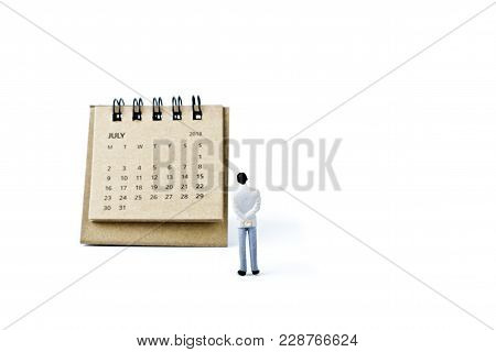July. Two Thousand Eighteen Year Calendar And Miniature Plastic Man On White Background.