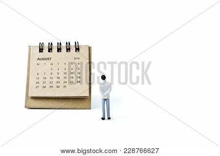 August. Two Thousand Eighteen Year Calendar And Miniature Plastic Man On White Background.