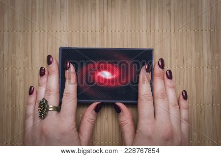 Fortune teller women hands is holding in hands a deck of tarot cards on desk table background. Futur