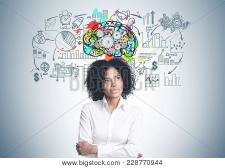 Portrait Of A Thoughtful African American Businesswoman Wearing A White Blouse And Standing With Cro