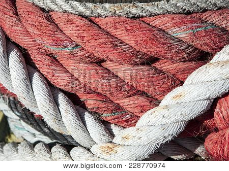 Nautical Background. Closeup Of An Old Red And White Frayed Boat Rope