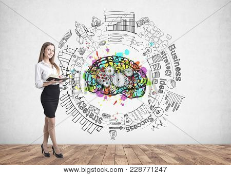 Portrait Of An Attractive Young Brunette Woman Looking Upwards At A Colorful Brain Sketch With Cogs