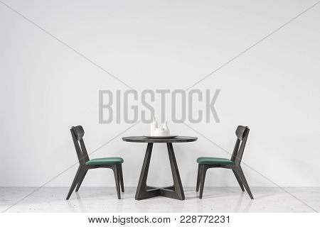 Round Table With Green And Black Wooden Chairs Near It Standing In An Empty Room With White Walls An