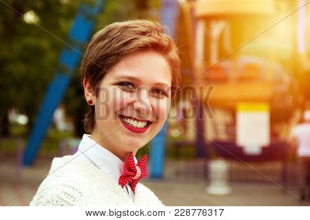 Short-cut Young Girl In An Amusement Park. The Work Of The Animator. Concert Make-up, A Charming Smi