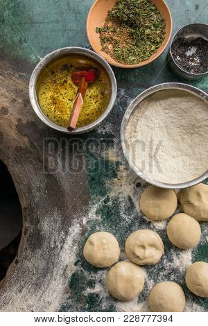 Ingredients for tandoori naan or roti - indian flat bread baked in clay oven. Oil, dough, flour and spices on the top of tandoori oven