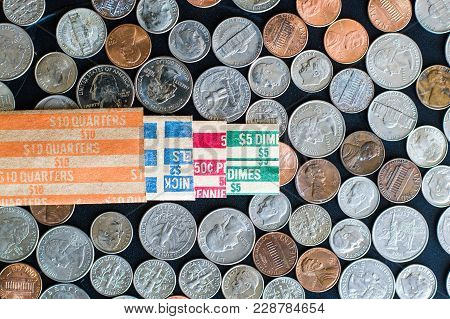 Us Coins On Flat Surface With Paper Rolls