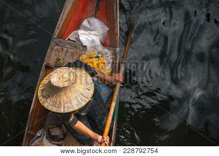 Trader with former times hat is paddle  rowboat. poster