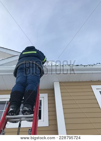 Man installing Christmas Lights on house