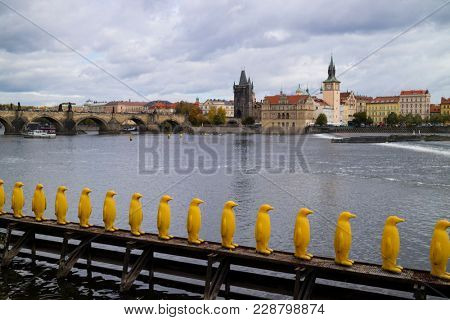 Prague, Czech Republic - October 9, 2017: Yellow plastic penguins outside Kampa Park near the Vltava River in Prague