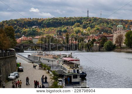 Prague, Czech Republic - October 8, 2017: Launches and tourists on the Moldau river in Prague in autumn with the lesser town in the background