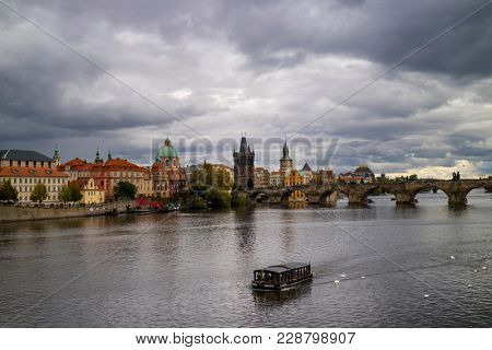 Prague, Czech Republic - October 8, 2017: Charles bridge seen to the towers and spires of the Old Town with a grey cloudy sky