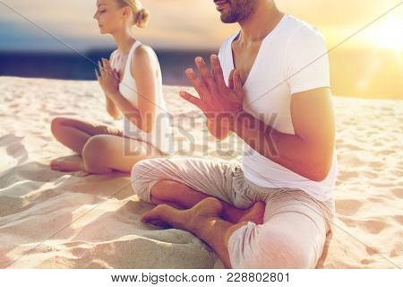 yoga , mindfulness, harmony and people concept - close up of couple meditating on beach