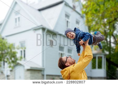 family, childhood and fatherhood concept - happy father and little son playing and having fun outdoors over house background