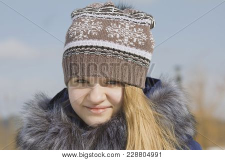 Portrait Of Teen Girl In Cap And Jacket With Fur Collar In Winter Outside, Youth Fashion