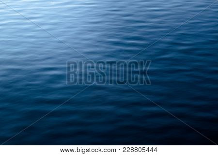 Ombre Blue Water With Sun Shining On Left And Deep Blue Water On Right With Ripple Design