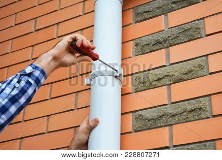 Worker Installing Rain Gutter Downspout Pipe. Contractor Hands Repair Rain Gutter Downspout Pipe Wit