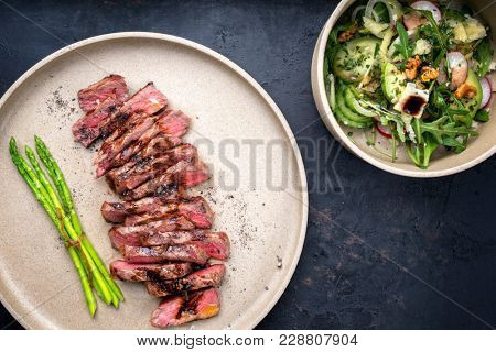 Traditional barbecue skirt steak sliced with green asparagus and salad as close-up on a plate