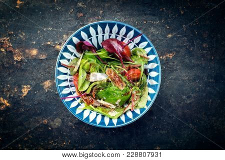 Traditional Italian lettuce with tomatoes and fig as top view on a plate with copy space