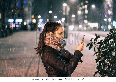 Stylish Woman Holding Phone In City Street. Smartphone In The Hands Of A Girl