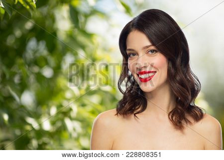 beauty, make up and people concept - happy smiling young woman with red lipstick over green natural background