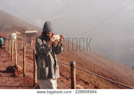 Girl Climbs The Path To The Mountain And Taking Pictures On The Phone